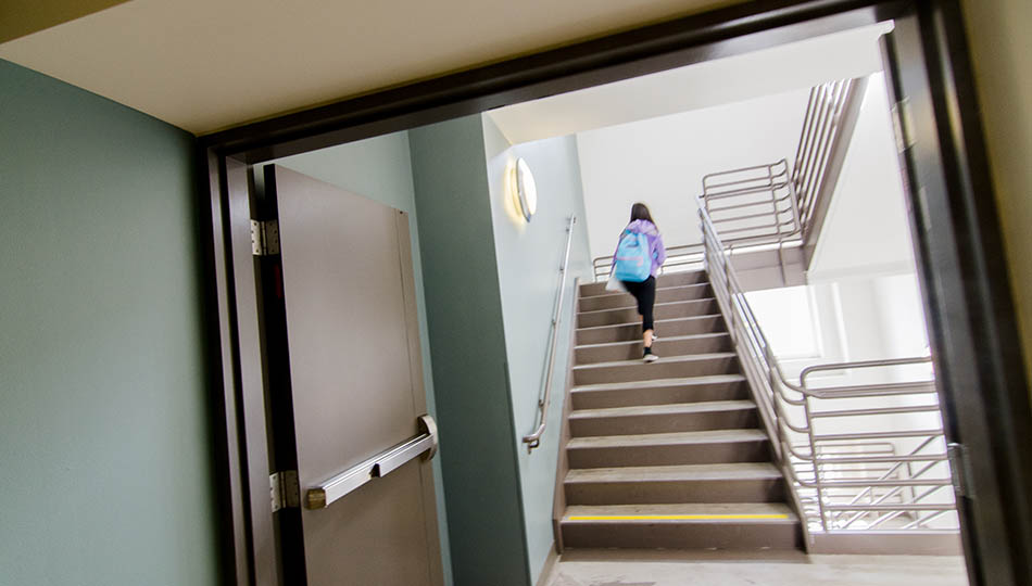 SFCM student walking up stairs inside 50 Oak building in San Francisco