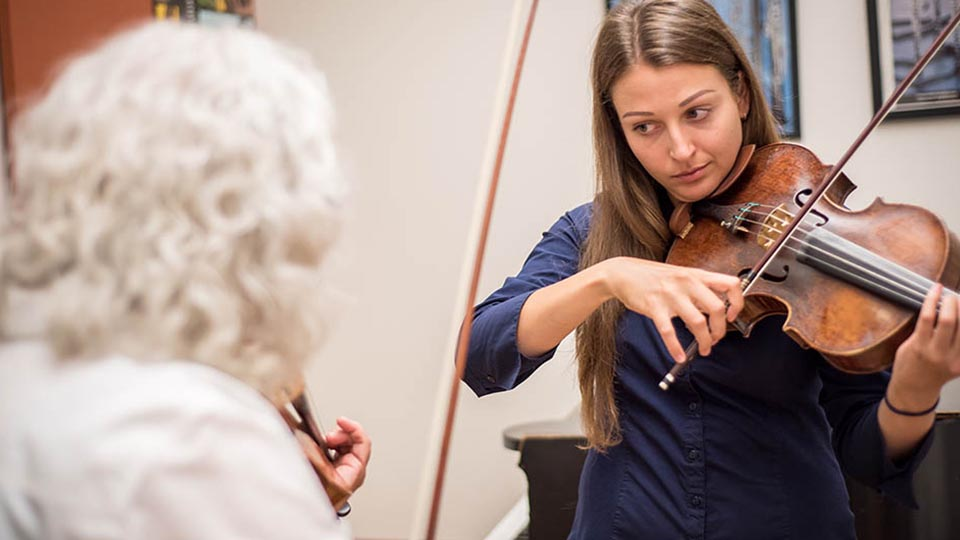 A San Francisco Conservatory of Music student playing viola during a lesson