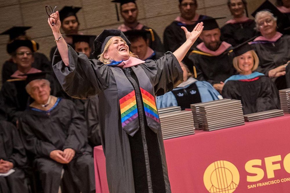 A woman wearing a graduation cap and gown with a rainbow stole smiles with her arms in the air