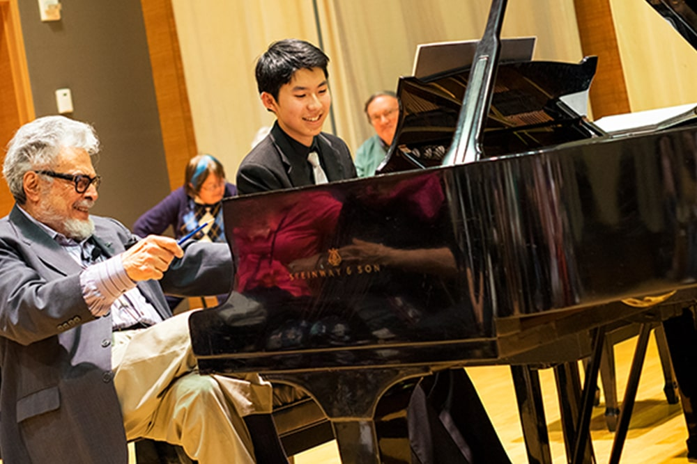 Piano student receiving lesson from professor in Osher Salon at 50 Oak St. Campus