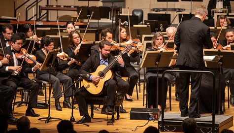 Solo guitarist plays in the front of an orchestra Winter term