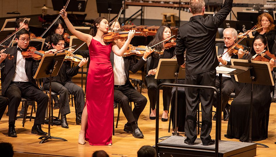 a solo violinist in a red dress plays in front of an orchestra