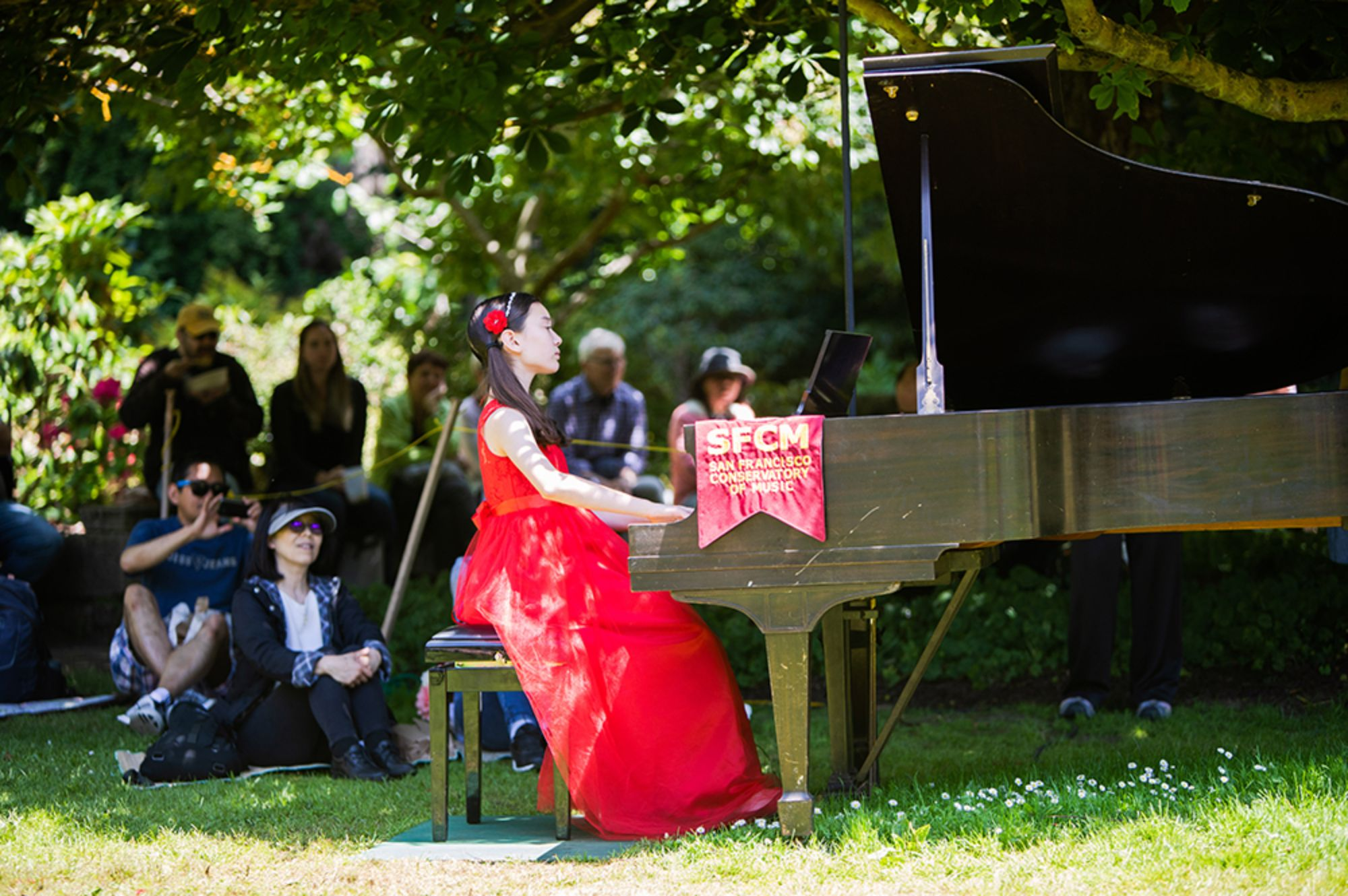 A summer pre-collage student plays the piano at an outdoor concert.  She is wearing a red dress and is surrounded by a small crowd of people smiling at her performance