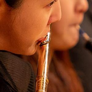 A SFCM student performing on the flute in the SFCM orchestra