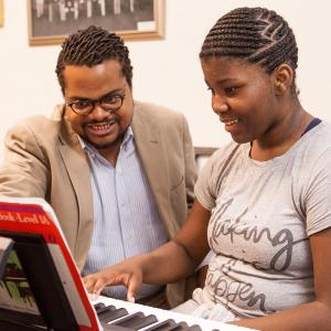 A male teacher with a female student at a keyboard with the teacher pointing to some sheet music