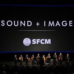 "A large, dark room with a huge screen with the text, ""Sound + Image"" and a brass brand before it"