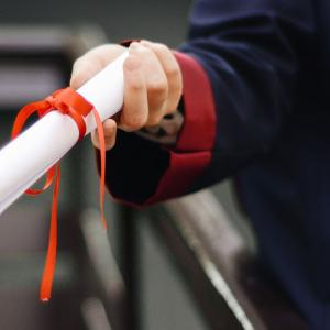 Person holding white commencement scroll