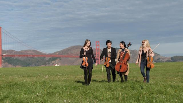 Two violinists, a violist, and a cellist walking on a green field with the golden gate bridge in the background