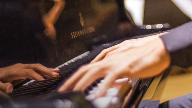 close picture of hands on the keys of a Steinway Piano
