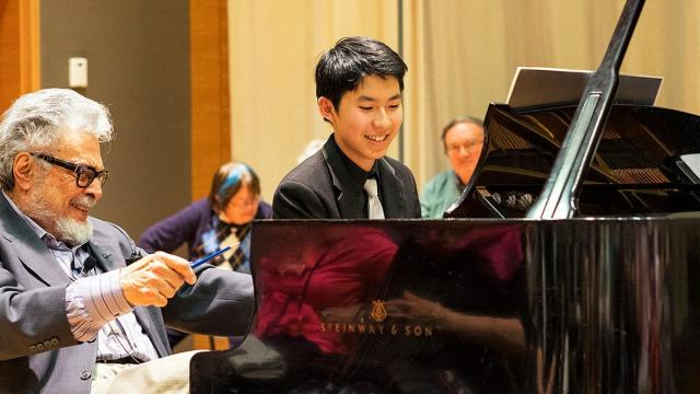 A pre-college student sits at a Steinway piano, a instructor sits next to him, they are both smiling