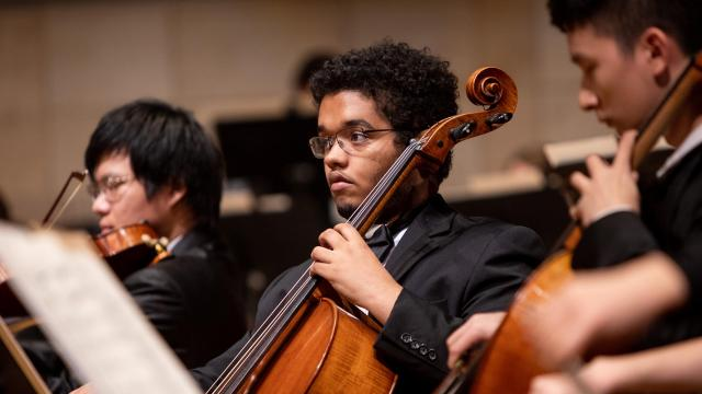 A SFCM student performing on the cello in the orchestra