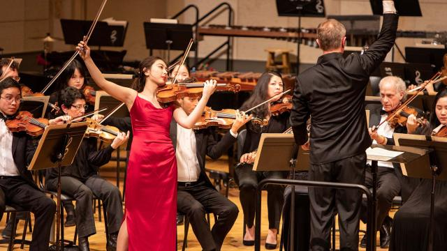 A SFCM student performing on the violin with the SFCM orchestra