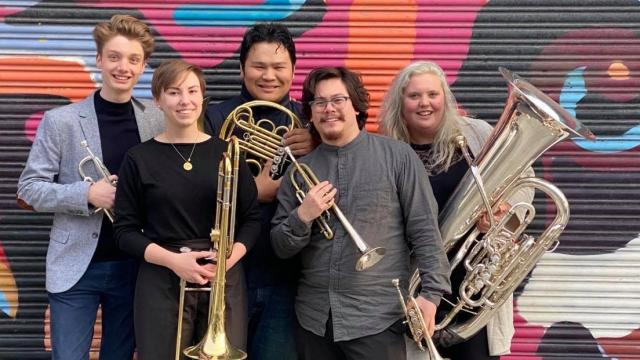 The Barbary Coast Brass Quintet stand with instruments in front of colorful wall