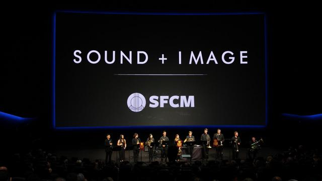 """A large, dark room with a huge screen with the text, """"Sound + Image"""" and a brass brand before it"""