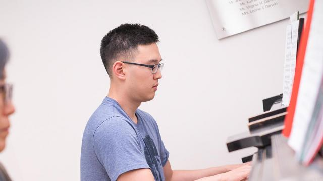 A photo of an adult extension student learning piano