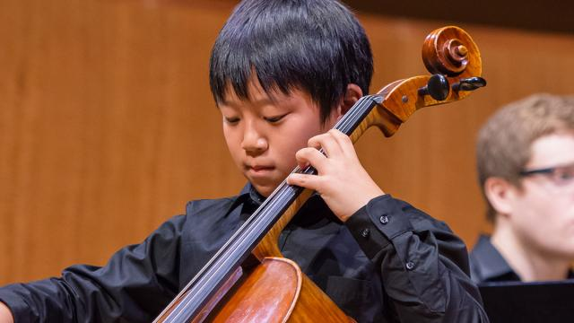 A pre-college student performing on the cello