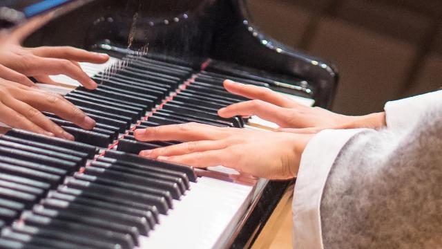Hands on the keyboard of a piano