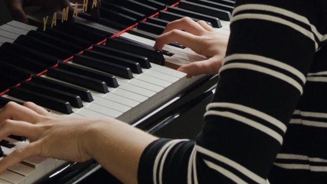 A pianists's hands as they play the piano