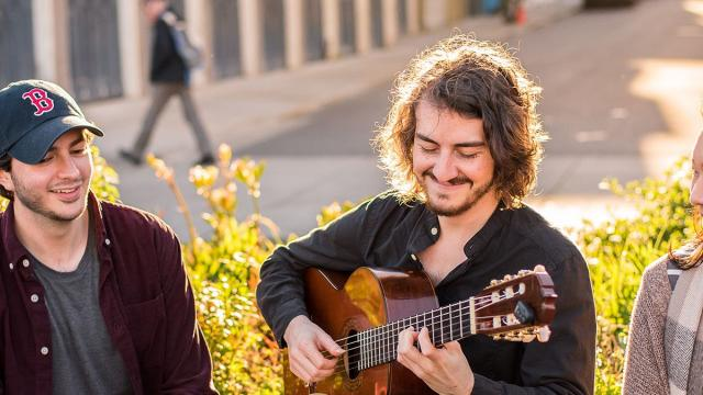 Student Life: three SFCM students, one playing guitar, sit outside together
